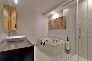 Salle de bain condo vue sur bain douche et vanité brun foncé et bois veiné
