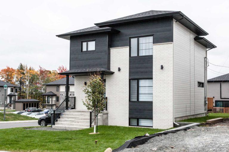 Construction de maison unifamiliale bois noir brique blanche